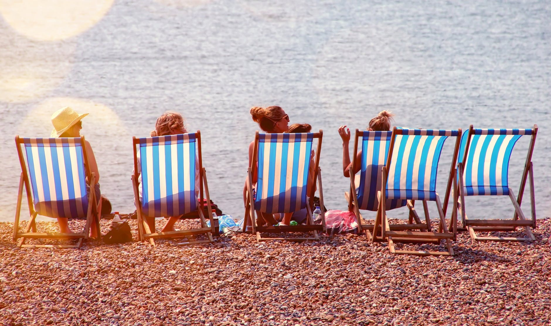 four people on lounge chairs near the beach