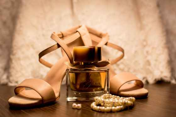 brown glass fragrance bottle beside white pearl bracelets