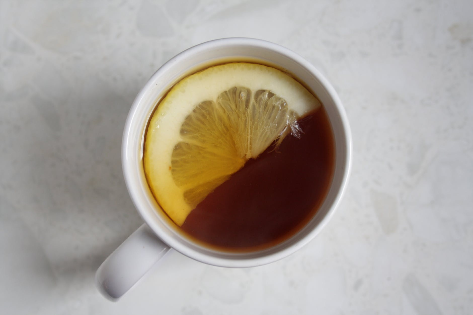 cup of tea with sliced lemon on white surface