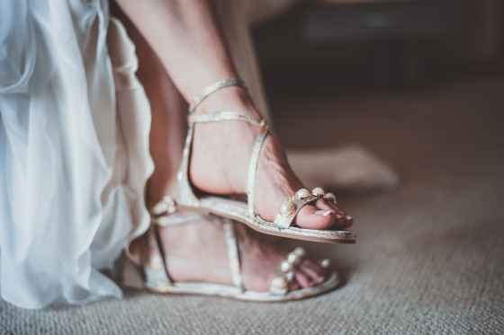 close up photo of woman wearing flat sandals