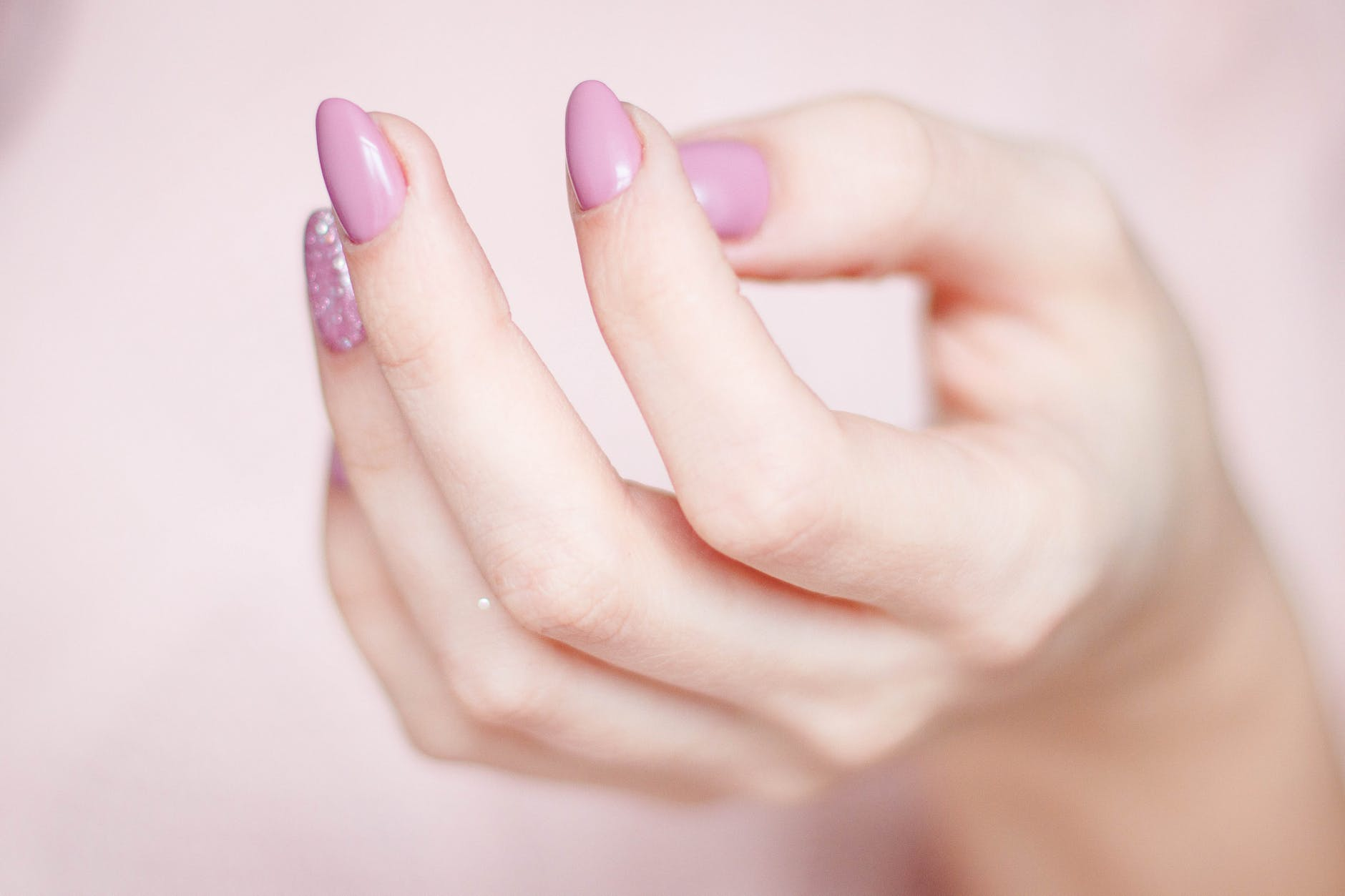 person s hand with pink manicure
