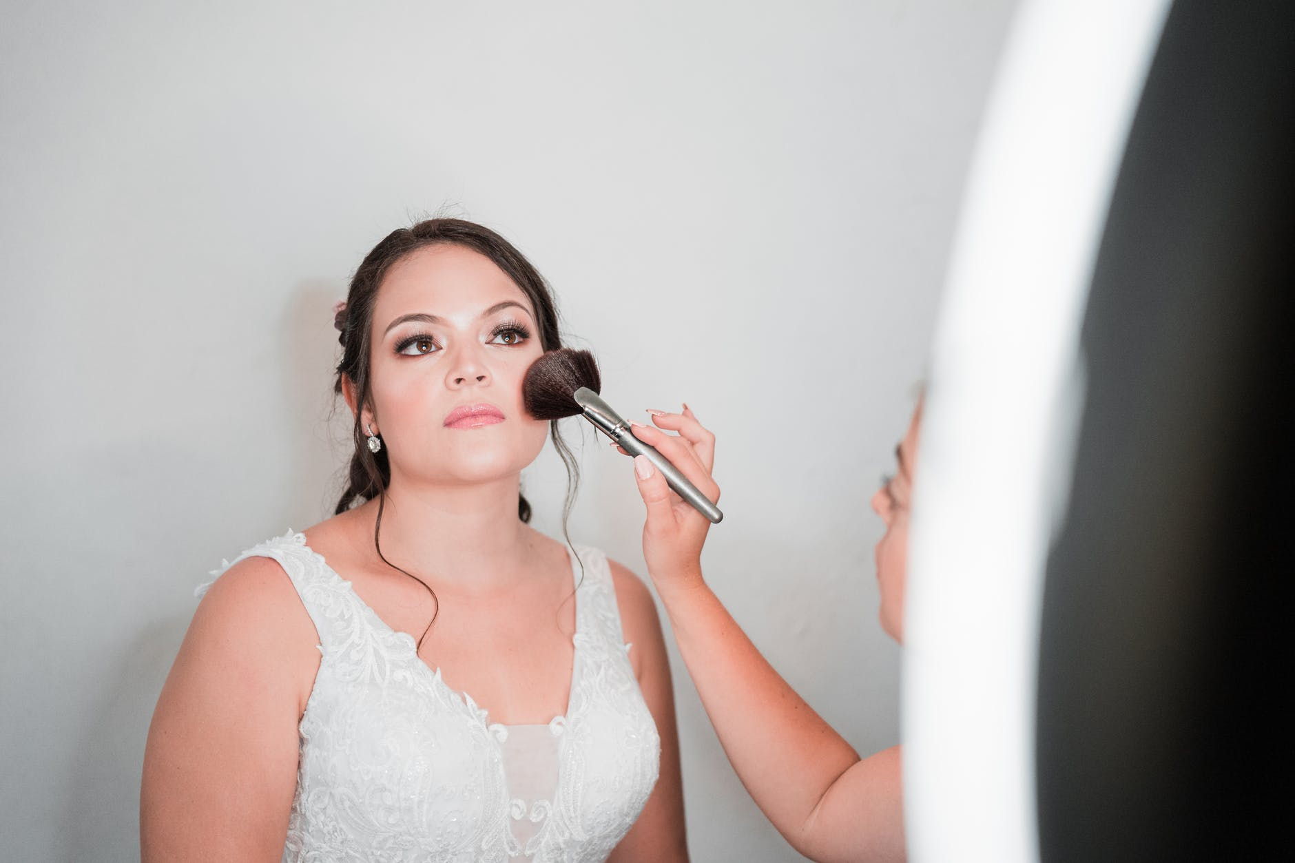 woman in bridal dress wearing makeup